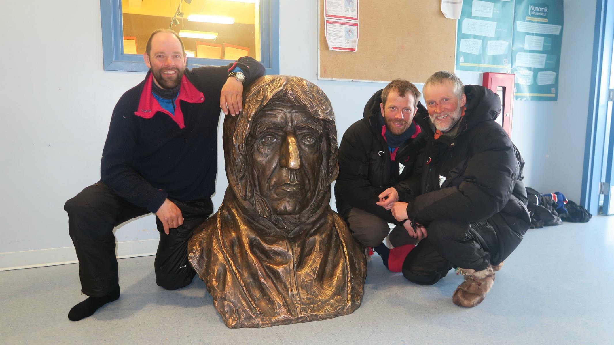 Tre menn sitter på huk rundt en byste av Roald Amundsen