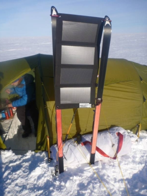Solar cell panel fastened between two cross country skis. Tent in the background.