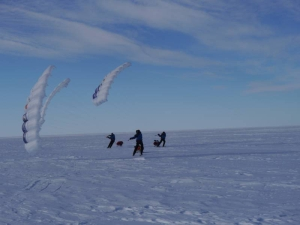 Three men with ski sails on the Ross ice shelf.