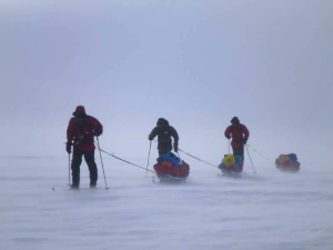 Three skiers agains the wind on the Ross Ice Shelf.