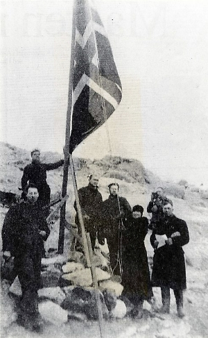 Caroline Mikkelsen raises the Norwegian flag at the cairn on Ingrid Christensen Land